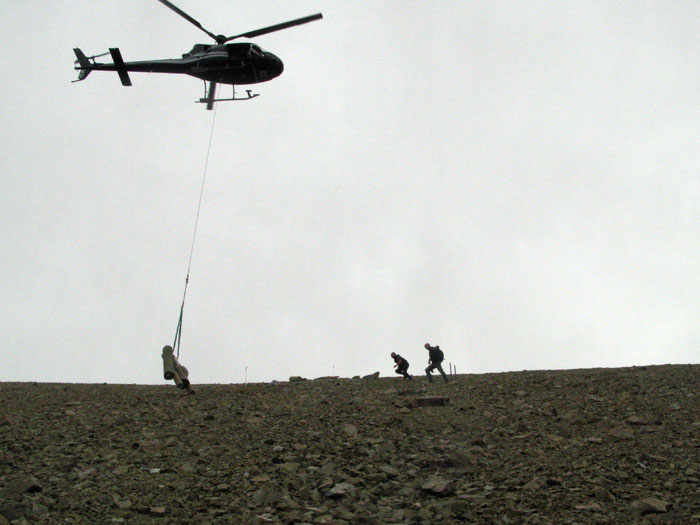 A helicopter lifts equipment for the lift to the construction team working on the lift line